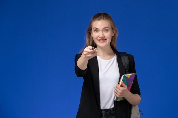 Studentessa di vista frontale in giacca nera che indossa zaino tenendo la penna e il quaderno con il sorriso sulla lezione di università college muro blu