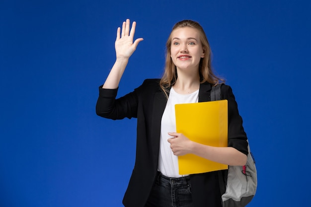 Front view female student in black jacket wearing backpack and holding yellow file waving on the blue wall school college university lessons