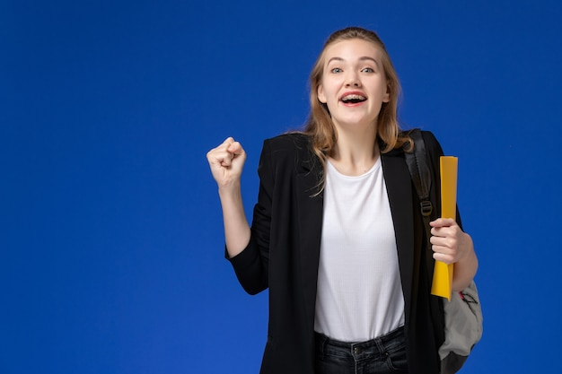 Front view female student in black jacket wearing backpack holding yellow files and rejoicing on blue wall school college university