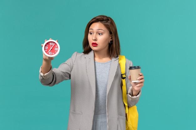 Vista frontale della studentessa in giacca grigia che indossa il suo zaino giallo con orologi e caffè sulla parete blu