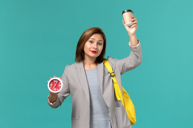Front view of female student in grey jacket wearing her yellow backpack holding clocks and coffee on blue wall