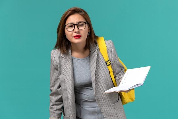 Vista frontale della studentessa in giacca grigia che indossa il suo zaino giallo che tiene il quaderno e la lettura sul muro azzurro