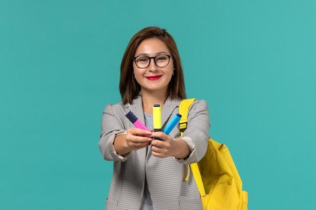 Vista frontale della studentessa in giacca grigia che indossa il suo zaino giallo con pennarelli sulla parete azzurra