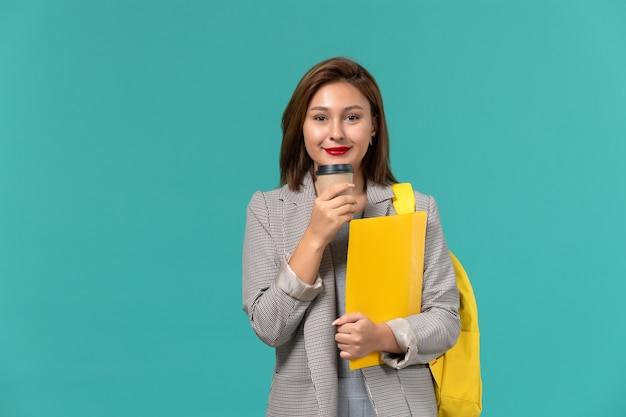 Vista frontale della studentessa in giacca grigia che indossa il suo zaino giallo con file e caffè sulla parete azzurra