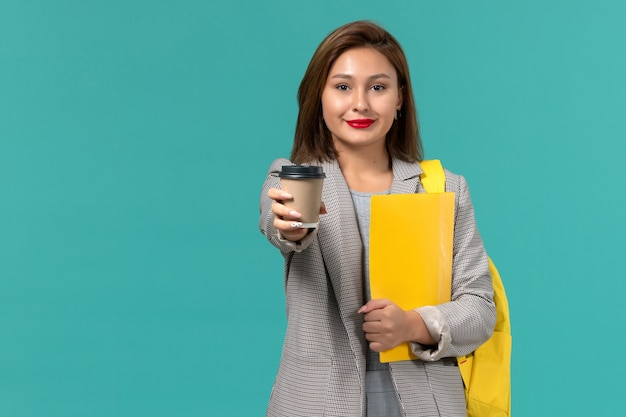 Front view of female student in grey jacket wearing her yellow backpack holding files and coffee on light-blue wall
