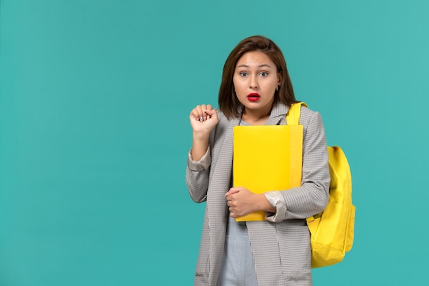 Front view of female student in grey jacket wearing her yellow backpack and holding files on light-blue wall