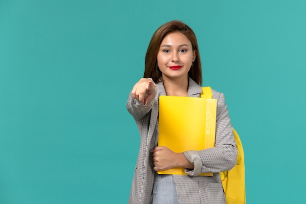 Vista frontale della studentessa in giacca grigia che indossa il suo zaino giallo e che tiene i file sul muro azzurro