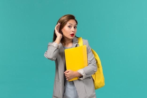 Vista frontale della studentessa in giacca grigia che indossa il suo zaino giallo e che tiene i file cercando di ascoltare sulla parete azzurra