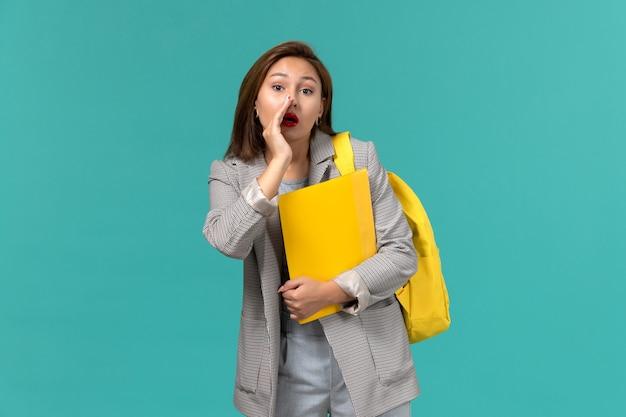 Vista frontale della studentessa in giacca grigia che indossa il suo zaino giallo e che tiene i file sussurrando sul muro azzurro