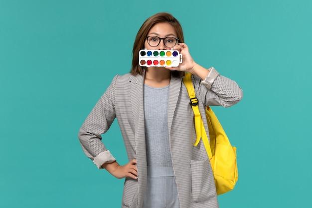 Vista frontale della studentessa in giacca grigia che indossa il suo zaino giallo con le vernici per disegnare sulla parete azzurra