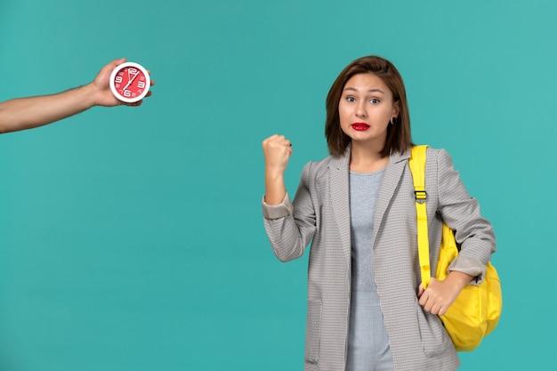Vista frontale della studentessa in giacca grigia che indossa uno zaino giallo sulla parete blu