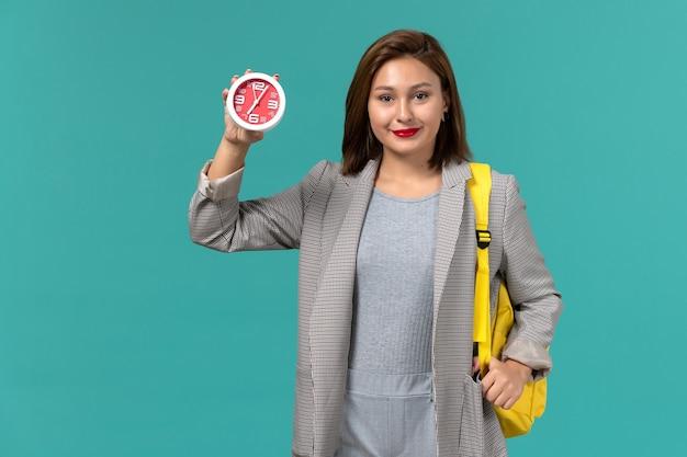 Vista frontale della studentessa in giacca grigia che indossa uno zaino giallo che tiene gli orologi sulla parete azzurra