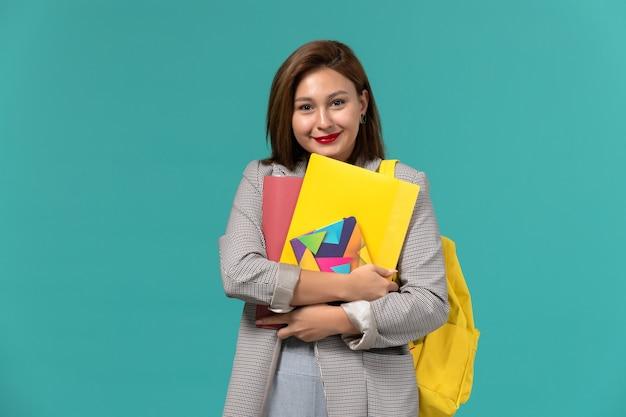 Vista frontale della studentessa in giacca grigia che indossa uno zaino giallo che tiene il quaderno e file sulla parete blu chiaro