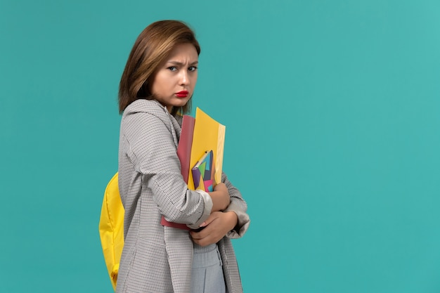 Front view of female student in grey jacket wearing yellow backpack holding copybook and files on the light blue wall