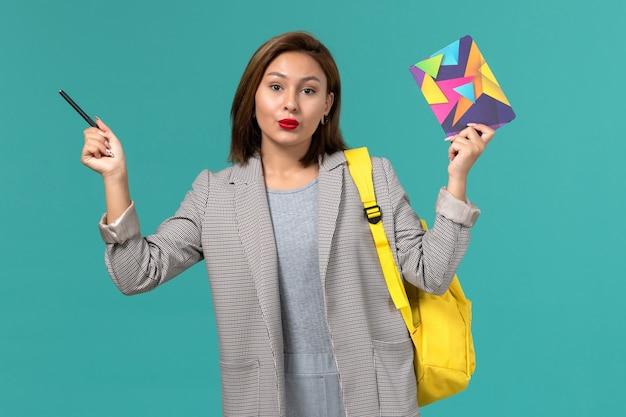 Vista frontale della studentessa in giacca grigia che indossa uno zaino giallo che tiene il quaderno sulla parete azzurra