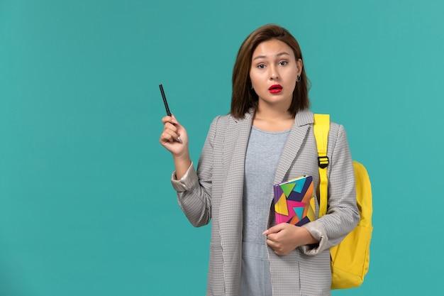 Vista frontale della studentessa in giacca grigia che indossa uno zaino giallo che tiene il quaderno con la penna sulla parete blu