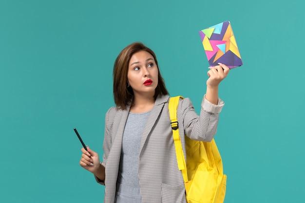 Vista frontale della studentessa in giacca grigia che indossa uno zaino giallo che tiene il quaderno con la penna sulla parete azzurra