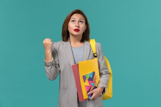 Vista frontale della studentessa in giacca grigia che indossa lo zaino giallo che tiene i file e il quaderno sulla parete blu