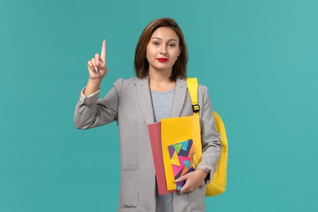 Vista frontale della studentessa in giacca grigia che indossa uno zaino giallo che tiene i file e il quaderno sulla parete azzurra