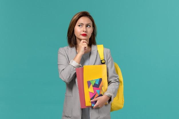 Vista frontale della studentessa in giacca grigia che indossa uno zaino giallo che tiene i file e il quaderno pensando sulla parete blu