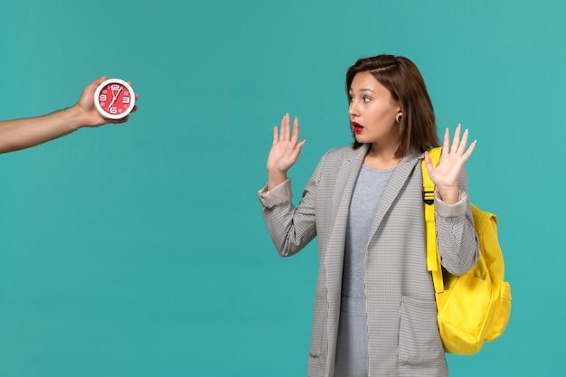 Vista frontale della studentessa in giacca grigia che indossa uno zaino giallo guardando gli orologi sulla parete azzurra