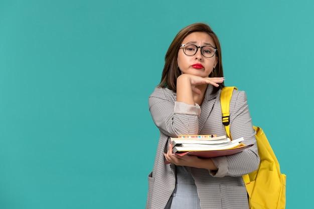Vista frontale della studentessa in zaino giallo giacca grigia che tiene i libri sulla parete blu
