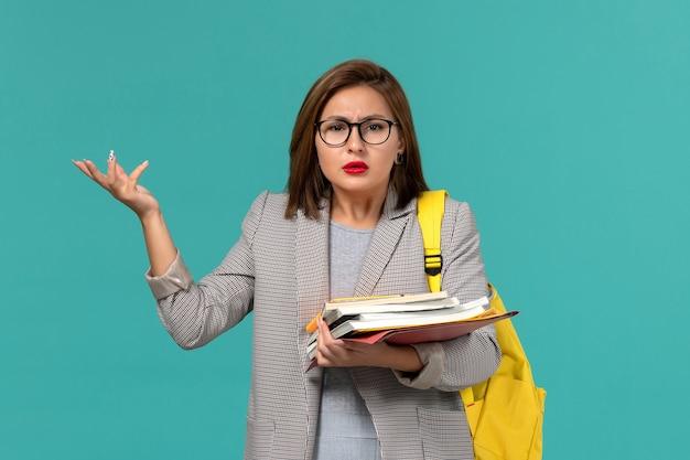 Vista frontale della studentessa in zaino giallo giacca grigia con libri sulla parete blu chiaro