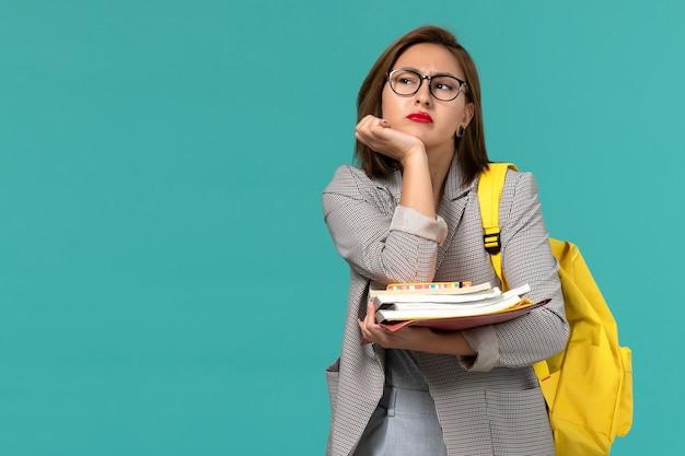 Vista frontale della studentessa in zaino giallo giacca grigia che tiene i libri pensando sulla parete blu