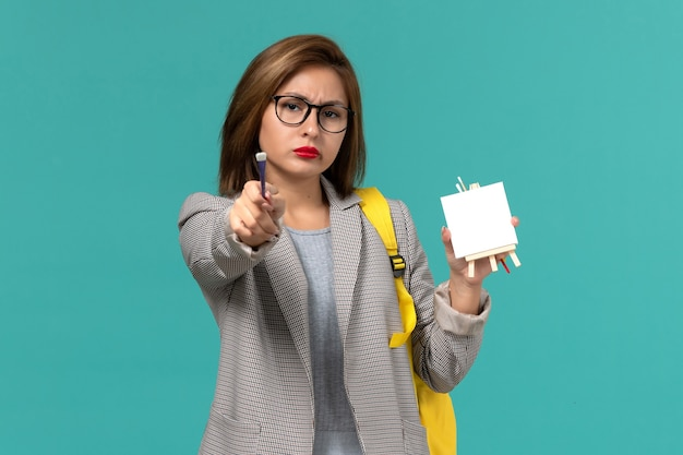 Vista frontale della studentessa in zaino giallo giacca grigia che tiene nappa e cavalletto sulla parete blu