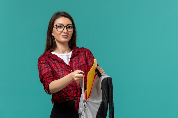 Front view of female student holding backpack and files on the light blue wall