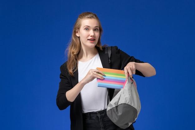 Вид спереди студентка в черной куртке, держащая серый рюкзак и тетрадь на синей стене, время уроков школы, колледжа, университета
