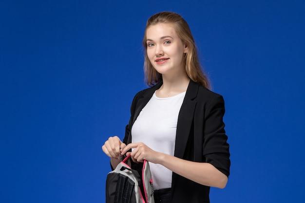 Вид спереди студентка в черной куртке держит серый рюкзак на синей стене урок школы колледжа университета