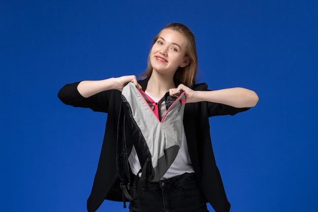 青い壁の学校の大学のレッスンで灰色のバックパックを保持している黒いジャケットの正面図女子学生