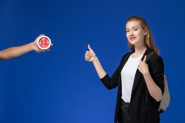 Вид спереди студентка в черной куртке носить рюкзак и улыбается на синей стене время уроков школы колледжа университета