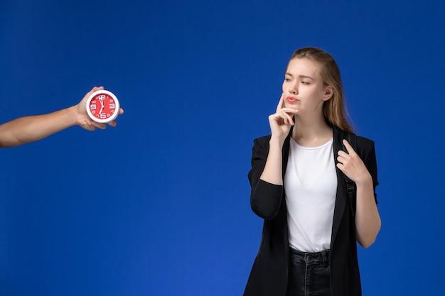 Вид спереди студентка в черной куртке, носить рюкзак и думать на синей стене, время уроков школы, колледжа, университета