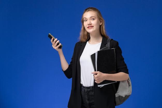 芸術学校の大学を描く青い壁に黒いファイルと電話を保持しているバックパックを身に着けている黒いジャケットの正面図女子学生