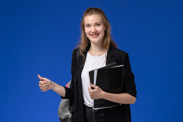 芸術学校の大学を描く青い壁に黒いファイルを保持しているバックパックを身に着けている黒いジャケットの正面図女子学生