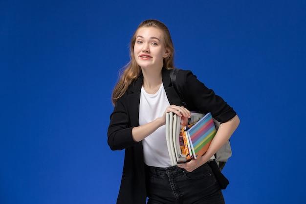 Вид спереди студентка в черной куртке в рюкзаке с книгами и улыбкой на синей стене урок школы университетский колледж