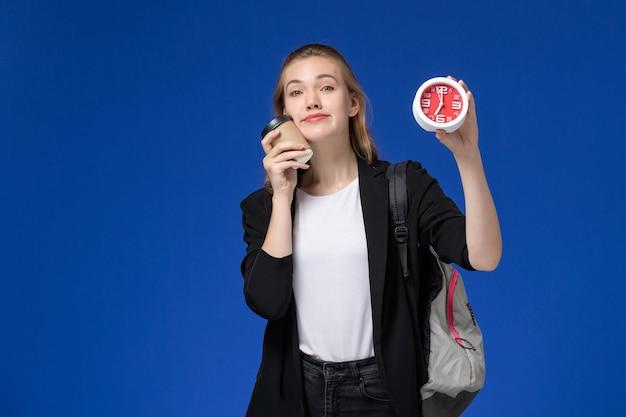Вид спереди студентка в черной куртке в рюкзаке с часами и кофе на синей стене школа колледж университет