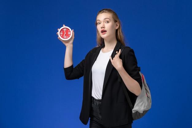 青い壁の大学のレッスンで時計を保持しているバックパックを身に着けている黒いジャケットの正面図の女子学生