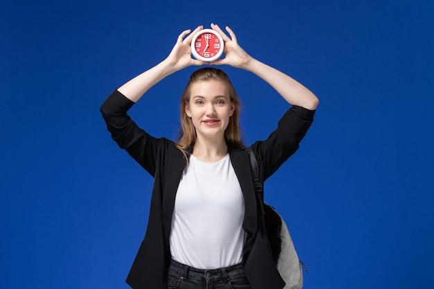 青い壁の学校の大学のレッスンで時計を保持しているバックパックを身に着けている黒いジャケットの正面図女子学生