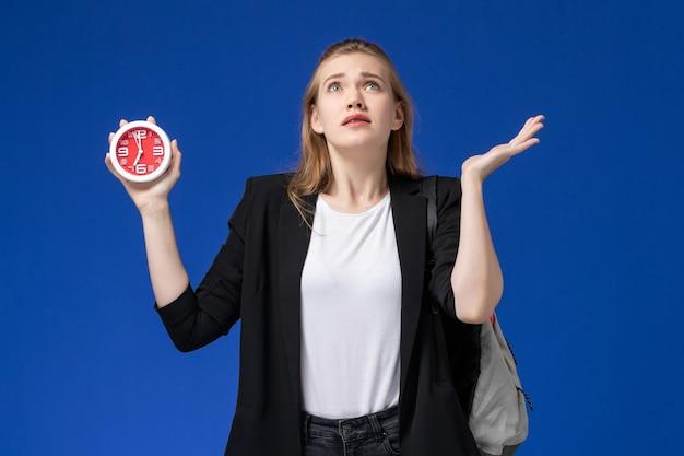 水色の壁の大学のレッスンで時計を保持しているバックパックを身に着けている黒いジャケットの正面図の女子学生