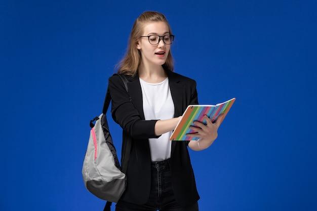 コピーブックを保持し、青い壁のレッスンを読んでバックパックを身に着けている黒いジャケットの正面図女子学生学校大学