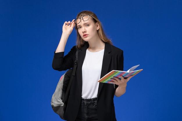 青い壁のレッスン学校大学大学でコピーブックを保持しているバックパックを身に着けている黒いジャケットの正面図女子学生