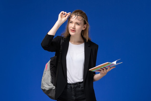 青い壁にコピーブックを保持しているバックパックを身に着けている黒いジャケットの正面図女子学生レッスンブック学校大学