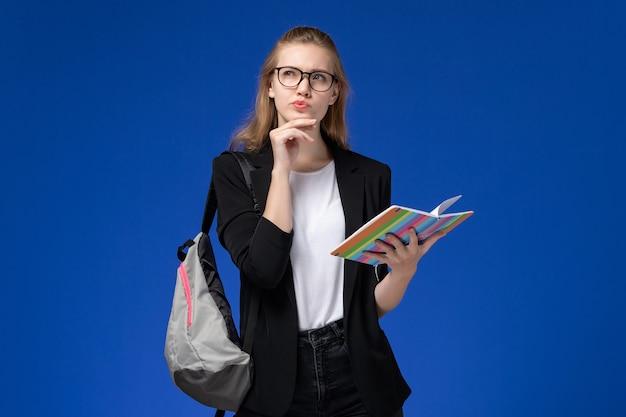 青い壁のレッスン学校大学大学で考えているコピーブックを保持しているバックパックを身に着けている黒いジャケットの正面図の女子学生