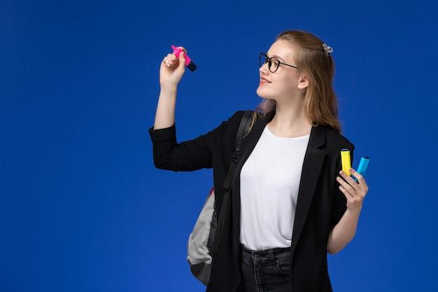 Вид спереди студентка в черной куртке в рюкзаке с фломастерами на голубой стене уроки школа колледж университет