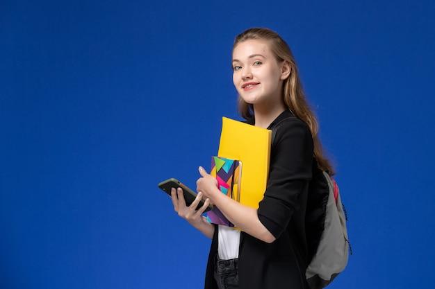 青い壁の本の学校の大学のレッスンでファイルとコピーブックを保持しているバックパックを身に着けている黒いジャケットの正面図女子学生