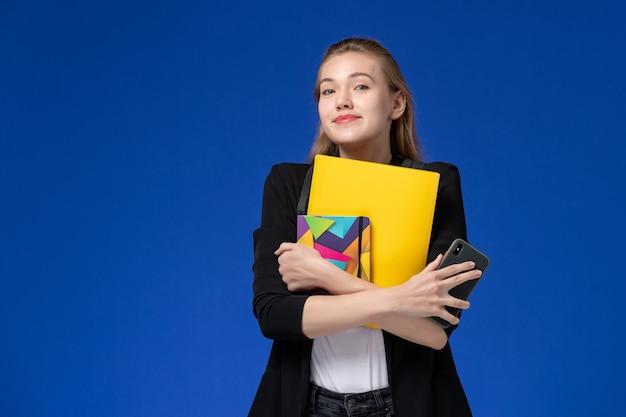 青い壁の本の学校の大学のレッスンでファイルとコピーブックを保持しているバックパックを身に着けている黒いジャケットの正面図の女子学生