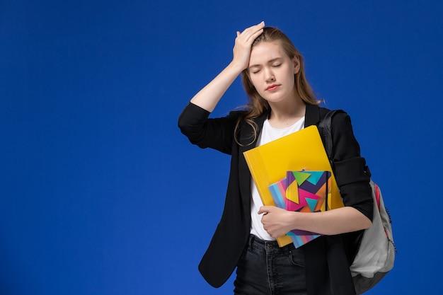 青い壁の大学のレッスンで頭痛を持っているコピーブックとファイルを保持しているバックパックを身に着けている黒いジャケットの正面図女子学生